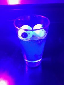 tonic water with plastic eye balls glowing under black light