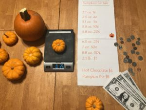 pumpkins on a table and scale with money and paper with cost per ounce of pumpkins