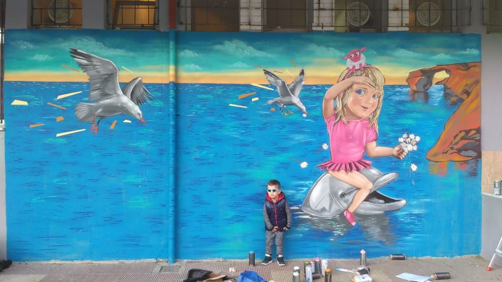 mural of girl riding a dolphin